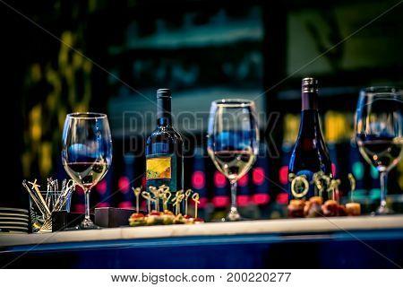 Snacks, glasses of wine and bottles on bartender counter in restaurant
