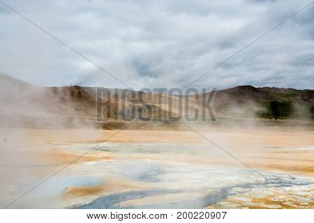 Mudpot in the Namafjall geothermal area, Iceland - area around boiling mud is multicolored and cracked.