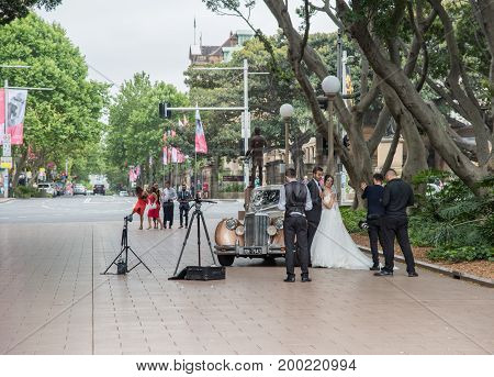 SYDNEY,NSW,AUSTRALIA-NOVEMBER 29,2016: Bride, Groom and wedding party at Hyde Park with photographer and vintage car in Sydney, Australia.