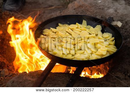 Potatoes fried in a frying pan in the open air .