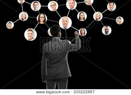 business, people, human resources, headhunting and technology concept - businessman with marker and network contacts icons from back over black background