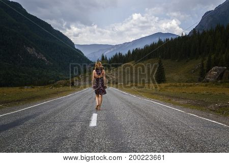 single barefoot woman is walking along the mountain road. Travel, tourism and people concept.