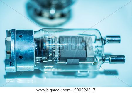 tube radio amplifier, preamplifier using 9-pins type valves close-up of tubes connect on circuit board on white socket surrounding with high voltage capacitors and resistors, white background