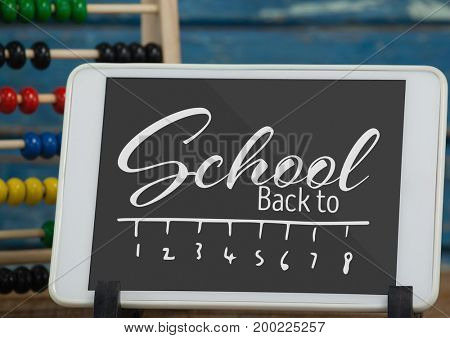Digital composite of Tablet on a school table with back to school text on screen