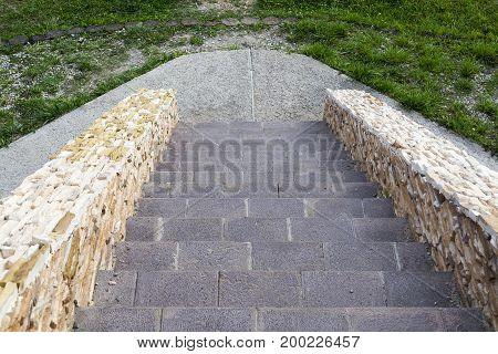 Down A Stone Staircase With Decorative Stones.