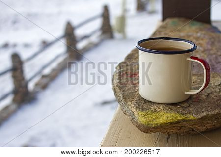 Enamel mug on a painted stone on a wooden veranda in winter on a rustic background.