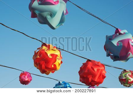 Colorful Twisted Plastic Lanterns Against Clear Blue Sky