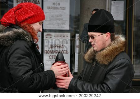 LUTSK UKRAINE - 04 January 2009: Priest sends Bethlehem fire girl scout