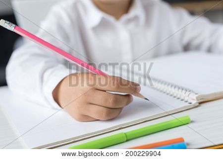 cropped shot of schoolgirl writing with pencil while doing homework