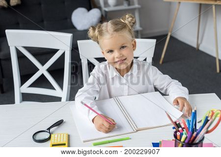 adorable little schoolgirl doing homework and smiling at camera