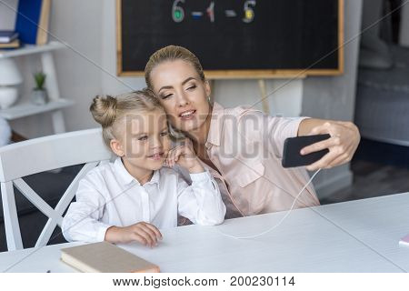 happy mother and daughter taking selfie with smartphone