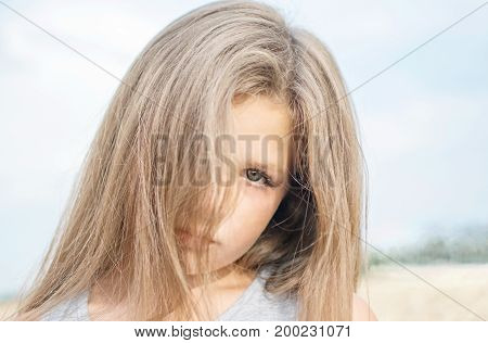 Portrait of adorable serene little girl with beautiful long hair on a summer day with blue sky background