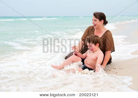Stock Photo: Young boy and his mom play in the surf at beach.