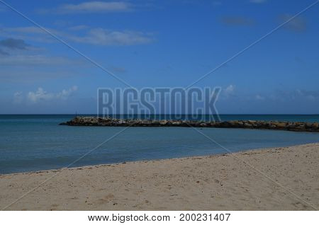 Aruba with a large rock jetty jutting into the ocean.
