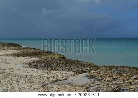Aruba with sand washed lava rocks on the coastline.
