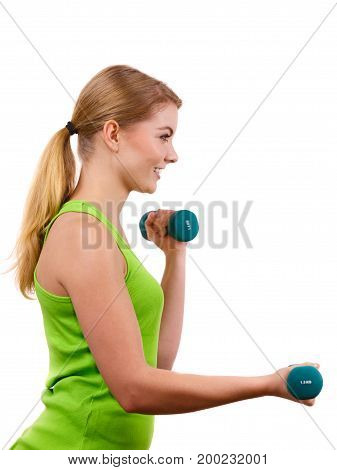 Woman exercising with dumbbells. Fit fitness blonde girl lifting light weights. Bodybuilding.