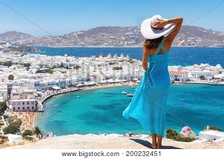 Attractive woman with blue dress enjoys the view over the town of Mykonos, Greece