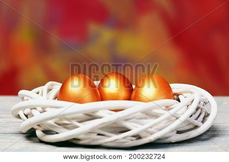Painted Easter Golden Eggs In Bird Nest On Colorful Background