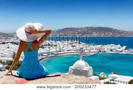 Elegant woman with blue dress and white hat enjoys the view over the town of Mykonos, Greece