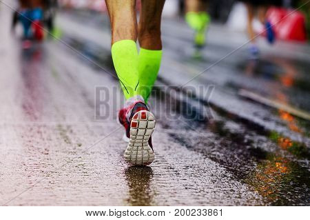 close up woman legs running on wet road in compression socks