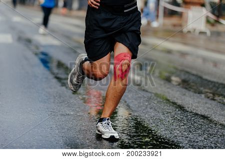 feet athlete man in kinesiotape knee running wet road