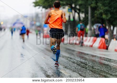 back man athlete runner running city marathon in rain