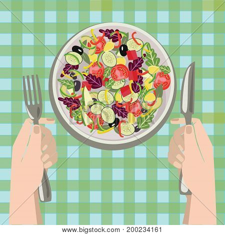 Hands with a knife and fork near a plate of vegetables salad on Salad bowl. Healthy fresh food in a plate and vegetables on a table cloth background.