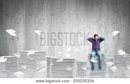 Young man in casual clothing sitting among flying paper planes with grey wall on background. Mixed media.