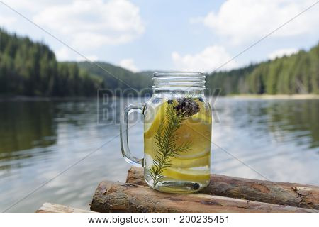 Infused water on a pier with lemon blueberries pine needles and cone