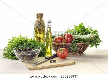Tomatoes, cucumbers, greenery and wild olives for salad on the table closeup