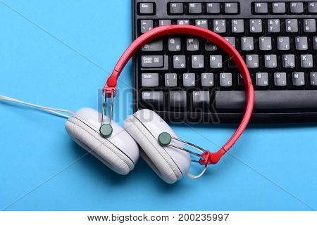Electronic Appliances On Turquoise Background. Headphones And Black Keyboard