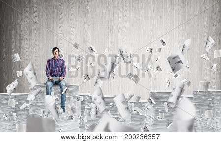 Young man in casual clothing sitting among flying paper documents with grey wall on background. Mixed media.