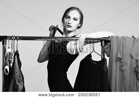 Pretty Girl Posing With Clothing On Hangers