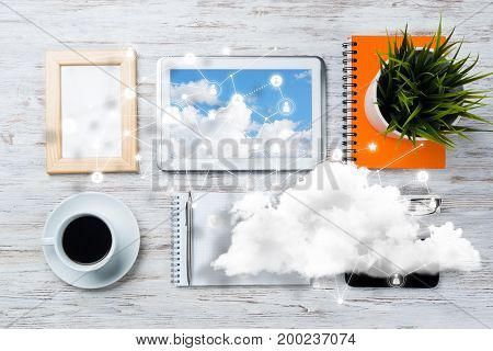 Top view of modern workplace with office stuff, social network connections and clouds above as symbol of still office life. Mixed media.