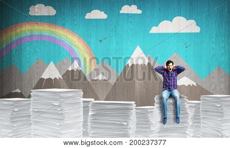 Attractive man in casual clothing sitting on pile of documents with sketched landscape view on background. Mixed media.