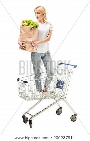 woman with paper bag in hands standing in shopping cart isolated on white