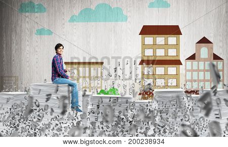 Attractive man in casual clothing sitting among flying letters with sketched cityscape view on background. Mixed media.