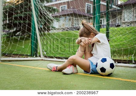 Crying ltittle girl who is playing football hiding her face while being upset to miss goal in gates. Pretty kid wearing white t-shirt jean shorts and sport shoes playing football. Children sport