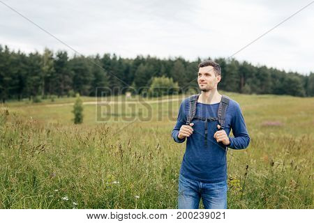 Young male traveler having tour across countryside, wearing sweater and jeans, keeping rucksack on his back, exploring unknown places. Handsome tourist having walk on summer field. Hiking concept
