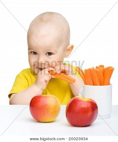 Cute Little Boy Eats Carrot And Apples