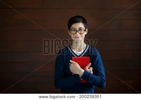 Attractive schoolboy in big glasses and elegant sweater, keeping red book in hands, going to read it. Little mixe race boy wearing spectacles, going to school, posing with red book into camera