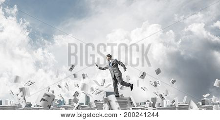 Businessman in suit running with phone in hand among flying paper documents with cloudly sky on background. Mixed media.