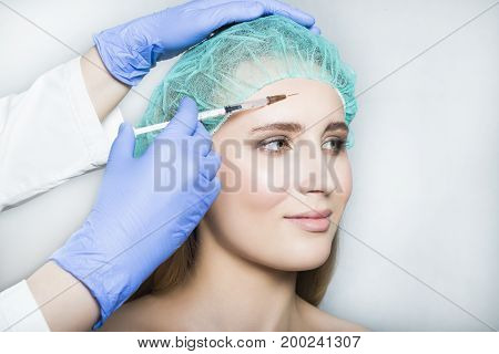 Doctor aesthetician in blue gloves makes beauty injections in the forehead of female patient in a green medical cap on white background