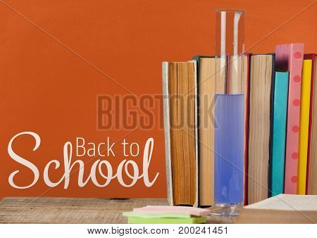 Digital composite of Books on the table against orange blackboard with back to school text