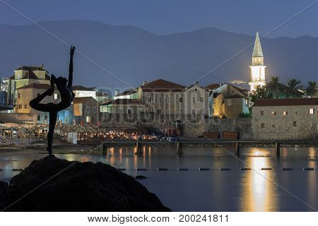 BUDVA MONTENEGRO - AUGUST 9 2014: Monument to the ballerina as a symbol of the city of Budva Montenegro against the background of the fortress at night