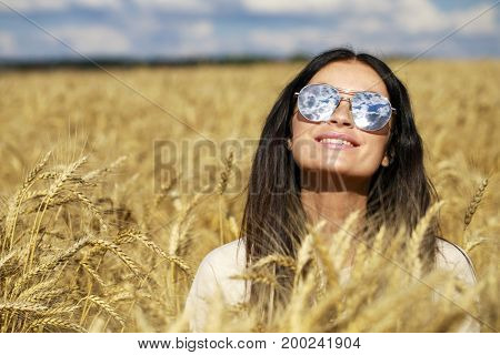 Portrait of a young woman in sunglasses with specular glasses in which white clouds are reflected