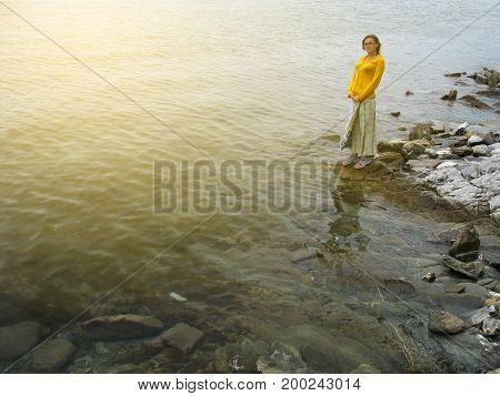 Girl on the edge of sea stays among stones with copy-space