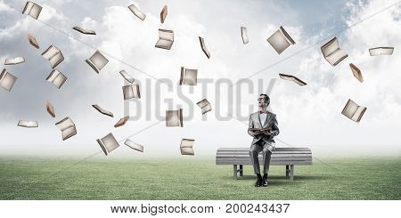 Funny man in red glasses and suit sitting on bench and reading book. Mixed media