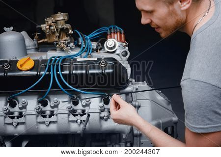 Close-up of an auto mechanic smiling repairing a lorry engine or a bus checking oil, concept repair in a garage, body shop.