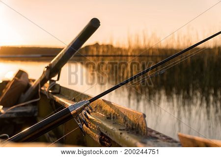 A Broken Fishing Rod Lies At The Side Of The Boat At Sunset